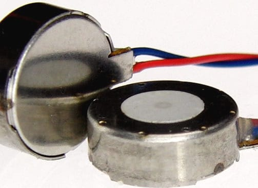 Two C10-100 LRA vibration motors. One is flat on the surface and one is on its side