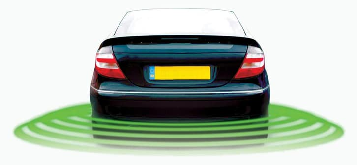 The back of a car with the car sensors in action collecting information for the driver