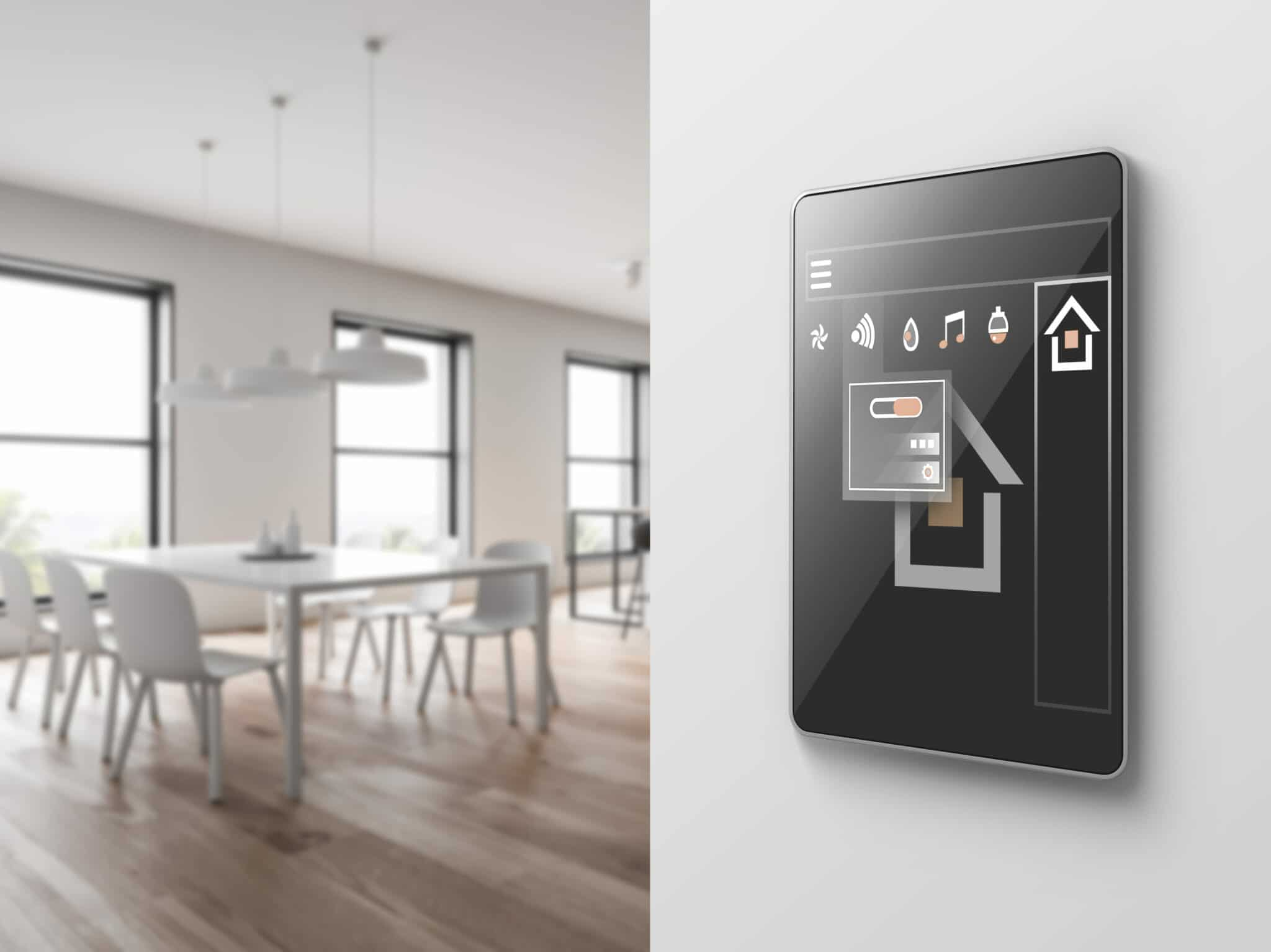 In the foreground there is a touchscreen control panel for smart blinds mounted to a wall. In the background is a dinning room with blinds installed in the windows.