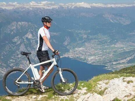 A cyclist stood on a mountain ridge with an e-bike.