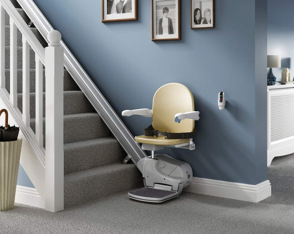 Mobility stairlift sat at the foot of a set of stairs in house