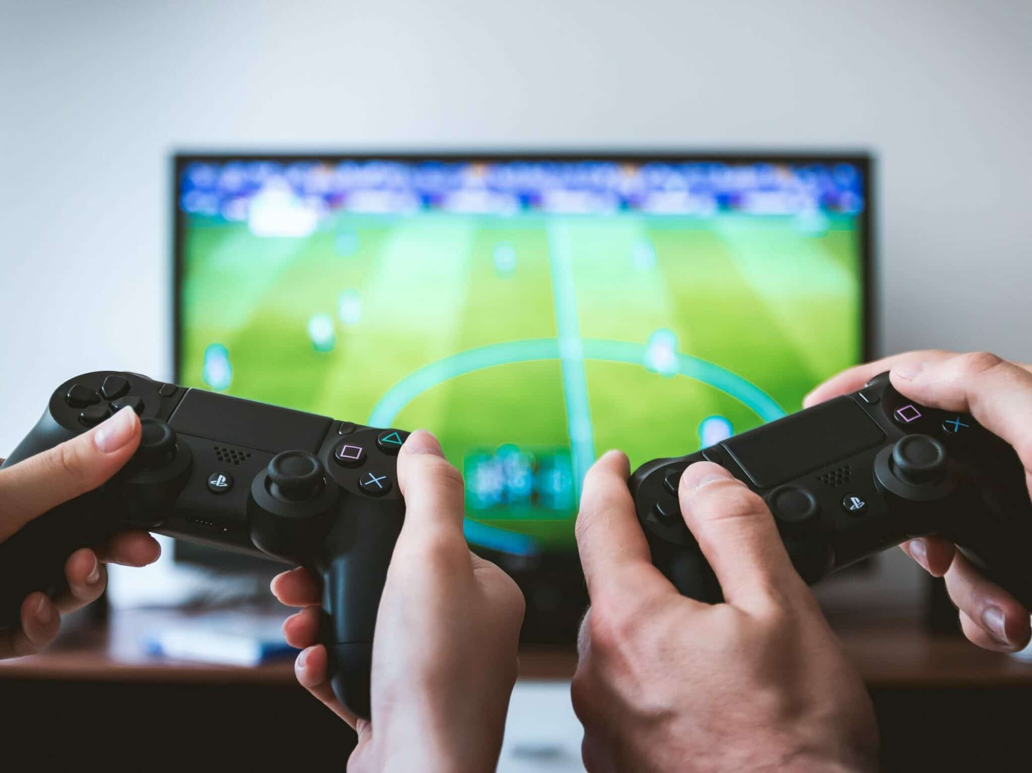 Two people holding video game controllers and in the background is a tv displaying the game they are playing